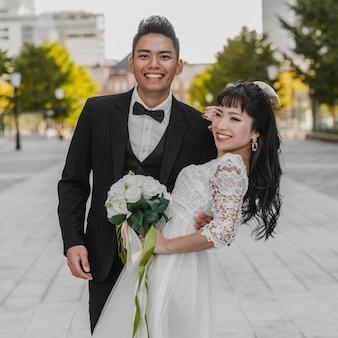 Noivo sorridente segurando a esposa na rua