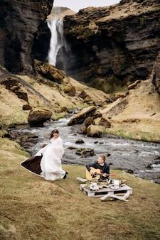 Noivo toca violão sentado perto do rio com a esposa