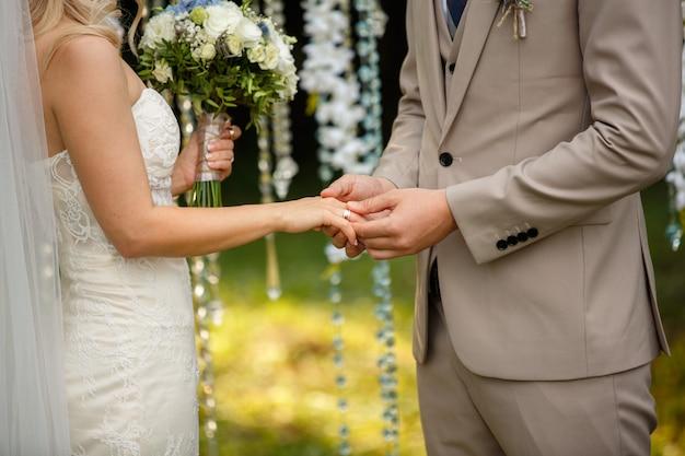 Noivo usa o anel no dedo da noiva, na cerimônia de casamento