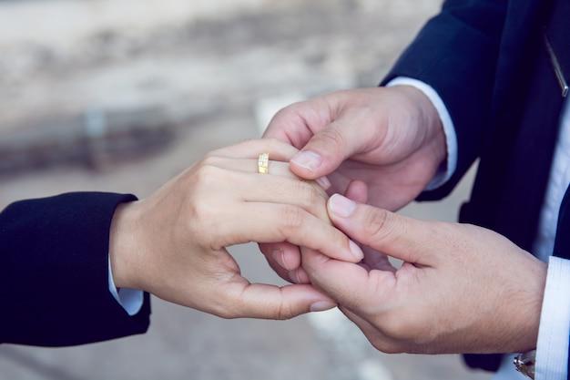 Noivo usa o anel no dedo da noiva