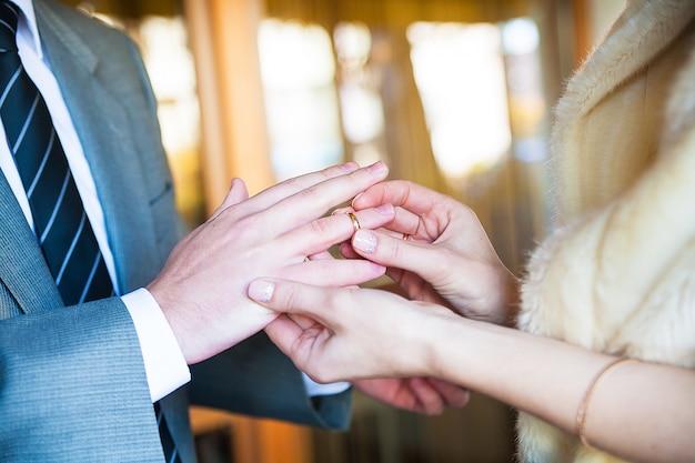 Noivo usa um anel no dedo de sua amada