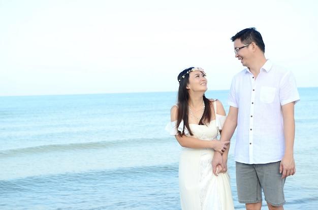 Noivos asiáticos em uma praia tropical. conceito de casamento e lua de mel.