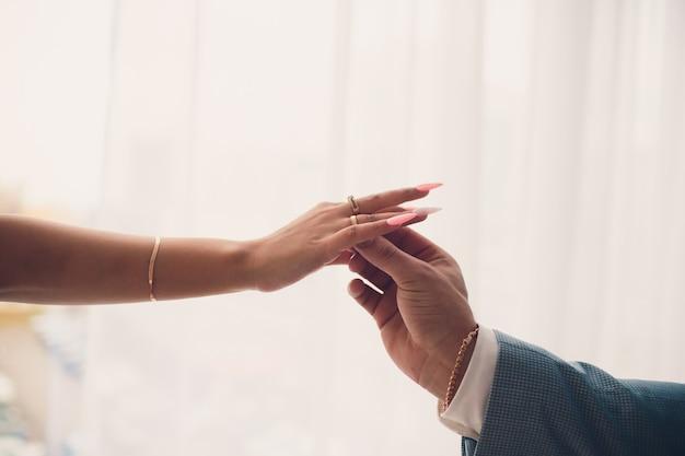 Noivos de mãos dadas, mostrando suas alianças. fundo branco.