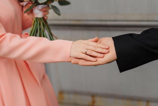 Noivos de mãos dadas na porta da igreja.