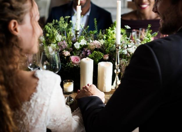 Noivos de mãos dadas uns aos outros na recepção do casamento