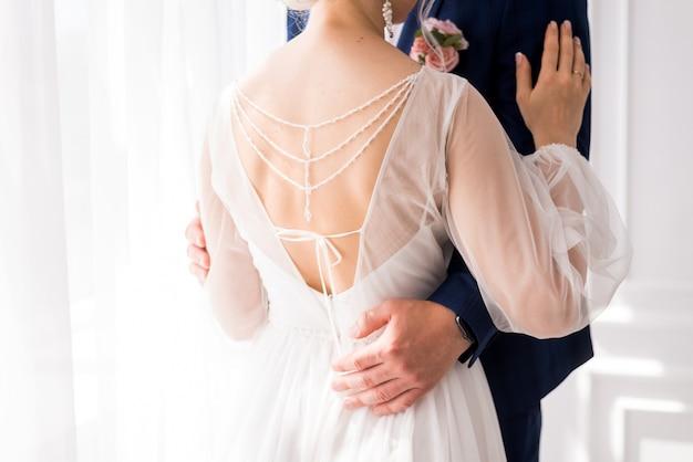 Noivos elegantes e lindos se abraçando, casal de noivos, vista de trás