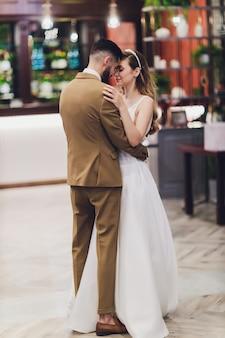 Noivos felizes à moda que levantam na palavra grande do amor na luz da noite na recepção de casamento fora. lindo casal de noivos se divertindo no parque à noite.