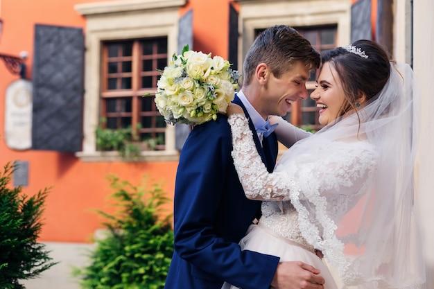 Noivos felizes abraçando e sorrindo sinceramente noiva segurando buquê de rosas