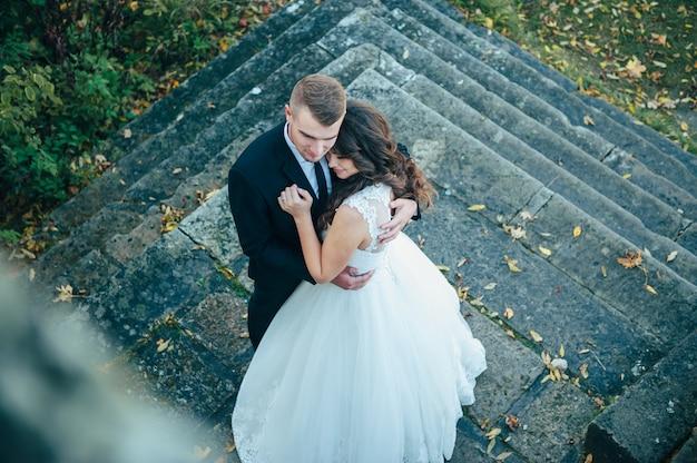 Noivos felizes e apaixonados caminham pelo parque de outono no dia do casamento