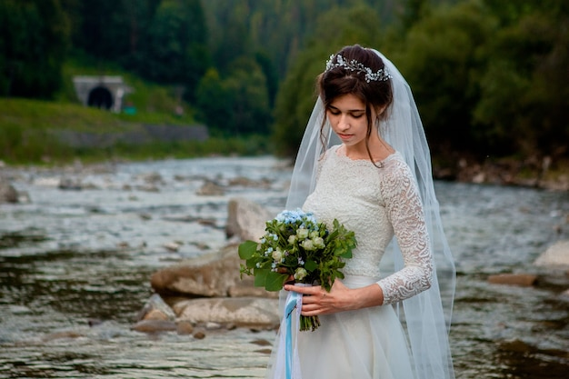 Noivos felizes em pé e sorrindo no rio