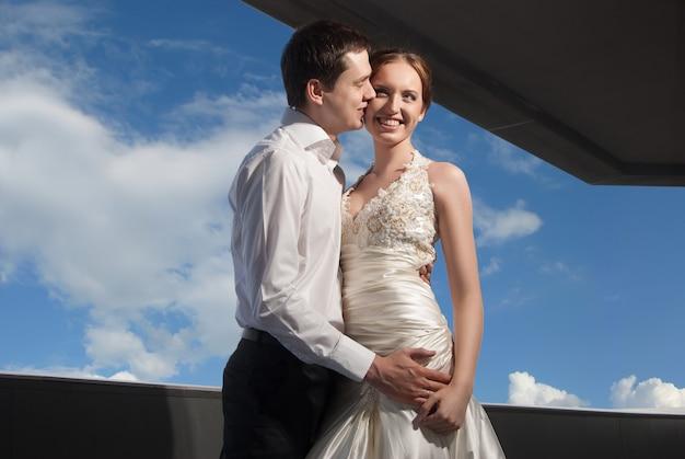Noivos felizes no casamento caminham na frente do céu azul na cidade