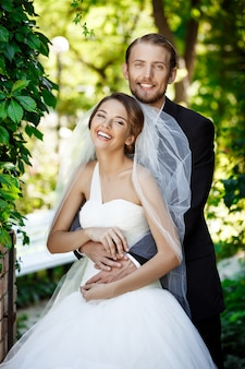 Noivos felizes sorrindo, abraçando, posando no parque.