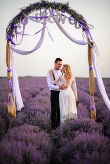 Noivos jovens e felizes se abraçando em um campo florido de lavanda