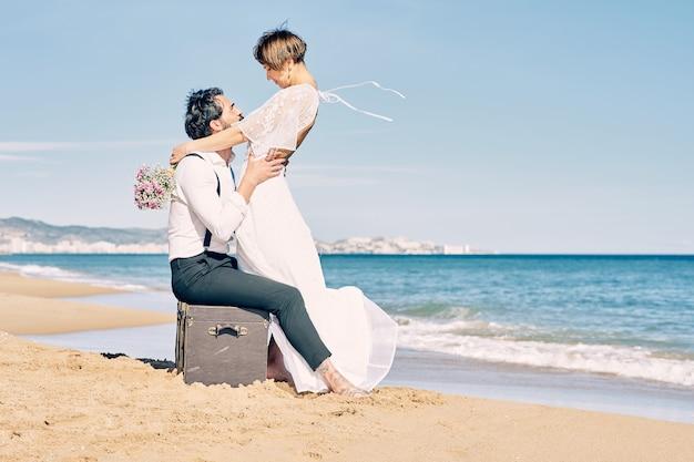 Noivos lindos na praia se olhando com muito amor e alegria