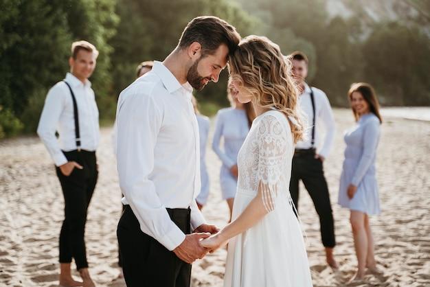 Noivos lindos se casando com convidados em uma praia