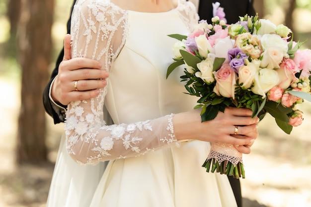 Noivos no dia do casamento, casal de noivos com buquê de flores