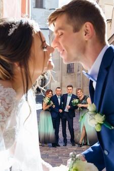 Noivos se beijam em primeiro plano damas de honra e padrinhos olham para os noivos