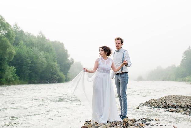 Noivos vestidos em estilo vintage de montanhas rochas na bela paisagem