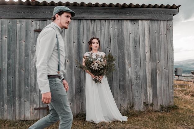 Noivos vestidos em estilo vintage, perto da parede de madeira cinza