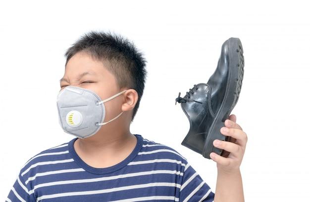 Nojo garoto segurando um par de sapatos de couro fedorento