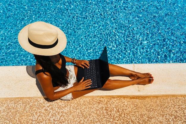 Nômade digital trabalhando com o laptop na piscina