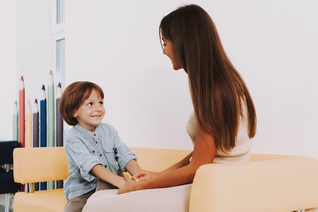 Nomeação para mãe pediatra segurando garoto mãos.