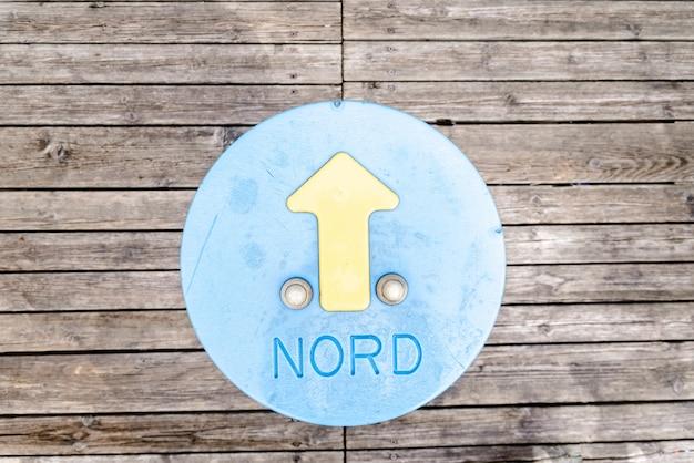 Nord palavra com seta de direção em um círculo pintado no chão de madeira