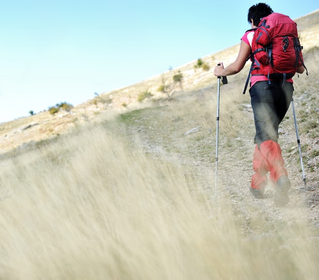 Nordic walking in mountains, hiking woman in grass