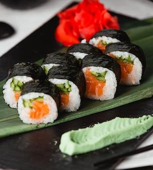 Nori de sushi com salmão e aperitivos ao redor.