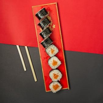 Nori de sushi na bandeja vermelha com pauzinhos de madeira.