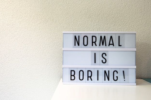 Normal é enfadonho, escrito em caixa de luz, sinal motivacional retrô home,