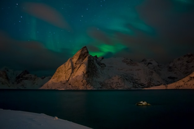 Noruega à noite. fiorde de inverno rodeado por montanhas cobertas de neve. luzes do norte e nuvens