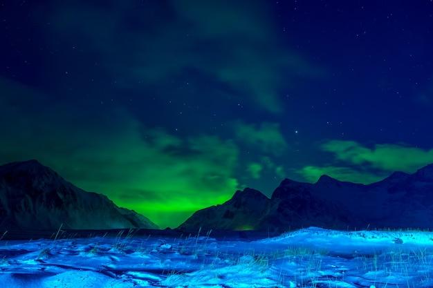 Noruega. lofoten. noite de inverno. grama e montanhas cobertas de neve. nuvens no céu e aurora boreal