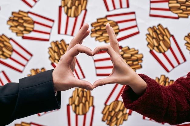 Nós amamos batatas fritas. coração de close-up de mãos para o fundo de parede de marca de rua. parede da marca desenhada com comida de rua. estação fria. jovem casal fazendo figura com as mãos