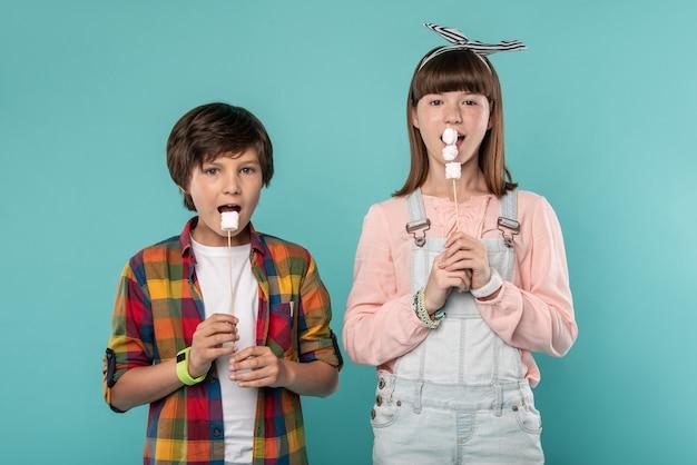 Nós amamos guloseimas. crianças alegres e encantadoras ao lado umas das outras comendo biscoitos