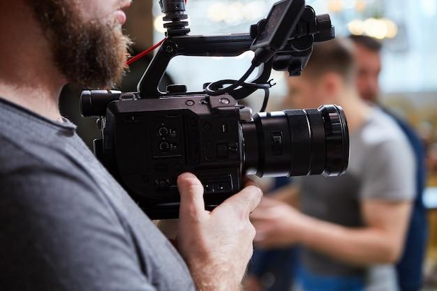 Nos bastidores da filmagem ou produção de vídeo e equipe de filmagem com equipamento de câmera
