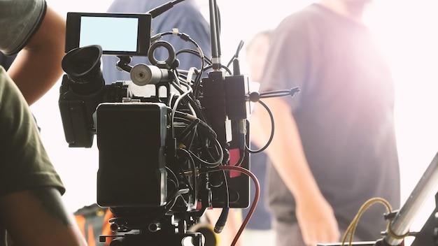 Nos bastidores da produção de vídeo no grande estúdio com equipamentos profissionais como tripé de câmera e guindaste.