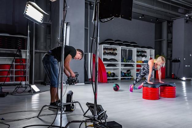 Nos bastidores da produção de vídeo ou filmagem de mulher no sportswear fazendo crossfit