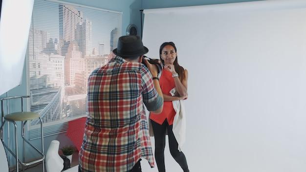 Nos bastidores da sessão de fotos: fotógrafo profissional trabalhando em estúdio, tirando fotos do modelo preto