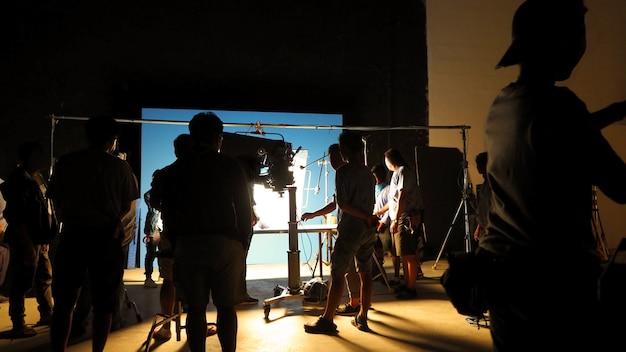 Nos bastidores do estúdio de filmagem de produção de vídeo em silhueta com profissionais