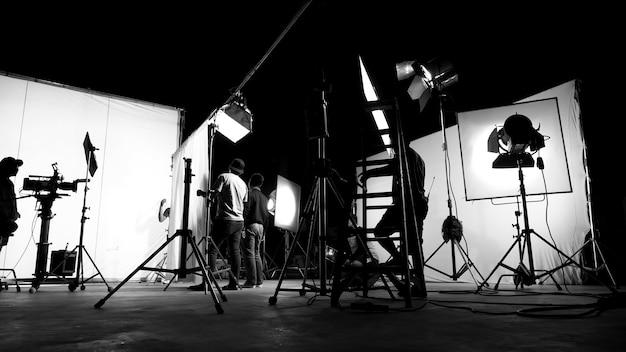 Nos bastidores do filme comercial de tv ou da produção de filmagem de vídeo, em que a equipe da equipe e o cinegrafista configuram uma tela verde para a técnica chroma key em um grande estúdio.