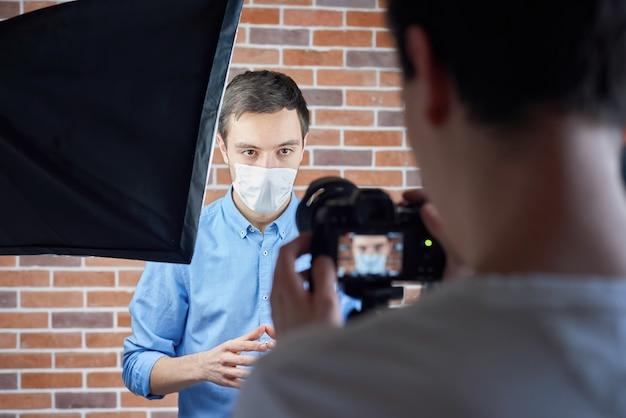 Nos bastidores do homem caucasiano falando com a câmera na máscara médica