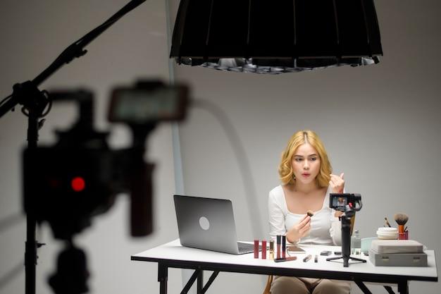 Nos bastidores, jovem empresária loira trabalhando com laptop apresenta produtos cosméticos durante uma transmissão ao vivo on-line em branco
