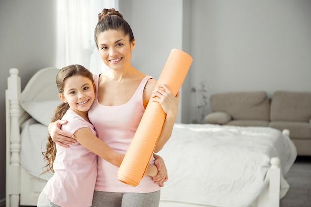 Nós estamos felizes. linda jovem mãe morena, alerta, segurando um tapete e abraçando a filha e elas usando roupas esportivas