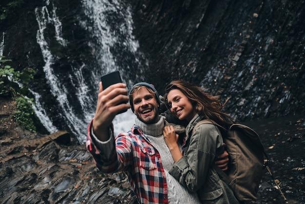 Nós estávamos aqui! lindo casal jovem tirando uma selfie em pé perto da cachoeira