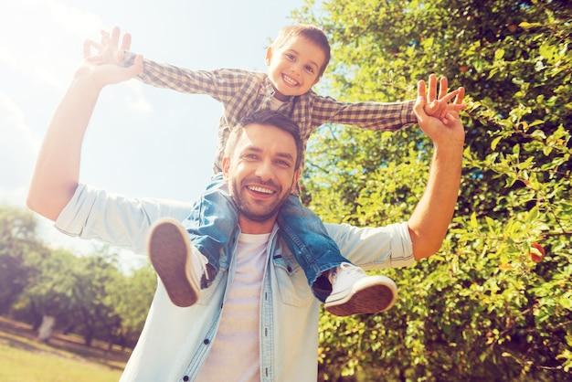Nós gostamos de passar tempo juntos! vista de baixo ângulo de um garotinho feliz estendendo as mãos enquanto o pai o carrega nos ombros