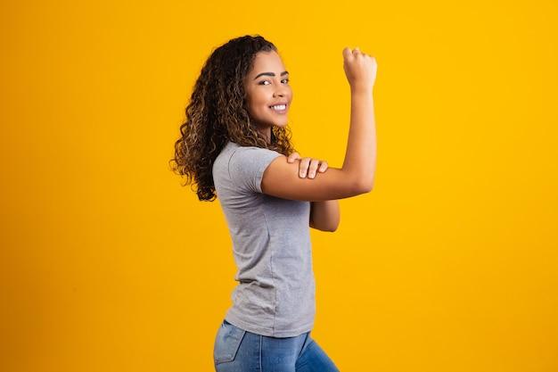 Nós podemos fazer isso. o punho feminino do poder feminino. mulher vítima de racismo. abuso no trabalho. o poder feminino. empoderamento feminino. a força das mulheres. fundo amarelo.