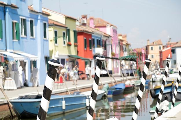 Nos postes em primeiro plano pintados com listras pretas e brancas no fundo (fora de foco) as casas coloridas da ilha de burano, em veneza, itália.
