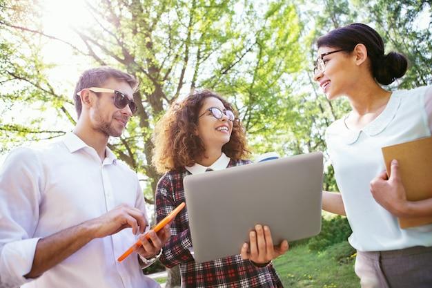 Nós somos amigos. contente senhora de cabelo encaracolado segurando seu laptop e seus amigos em pé perto dela