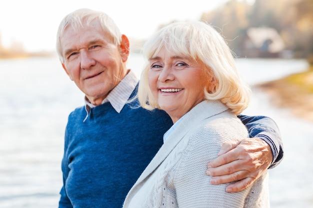 Nós somos felizes juntos. casal de idosos felizes se unindo e sorrindo enquanto estão juntos no cais